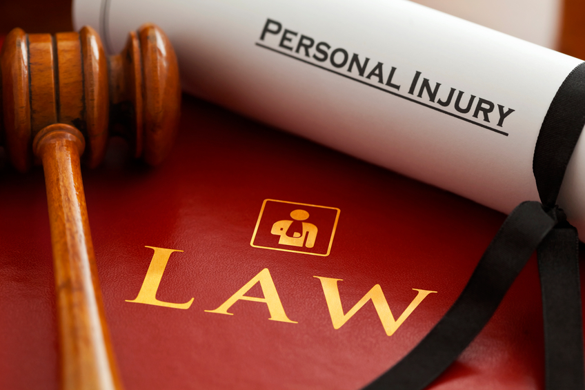 Red leather Personal Injury Law book and gavel with gold embossed type and stylised icon of figure with arm in a sling embossed on the book cover and a Personal Injury writ.